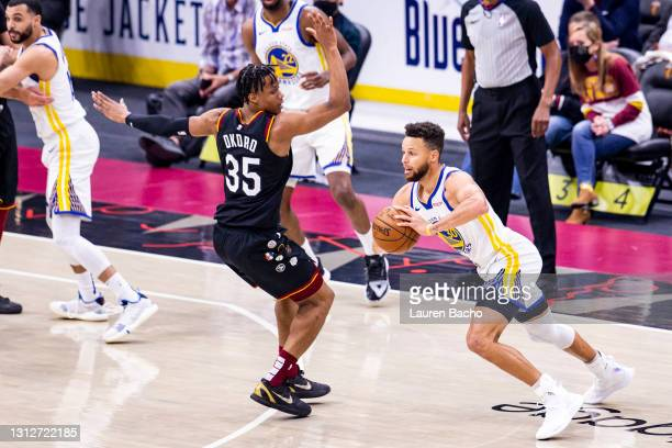Stephen Curry of the Golden State Warriors passes the ball around Isaac Okoro of the Cleveland Cavaliers during the second quarter at Rocket Mortgage...