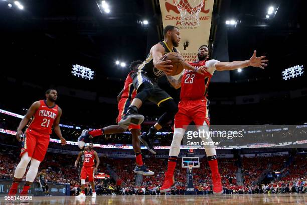 Stephen Curry of the Golden State Warriors passes the ball around Anthony Davis of the New Orleans Pelicans during Game Four of the Western...