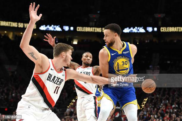 Stephen Curry of the Golden State Warriors passes the ball behind his back against Meyers Leonard and Damian Lillard of the Portland Trail Blazers...