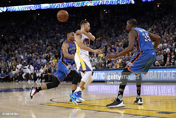 Stephen Curry of the Golden State Warriors passes the ball while guarded by Russell Westbrook and Kevin Durant of the Oklahoma City Thunder at ORACLE...