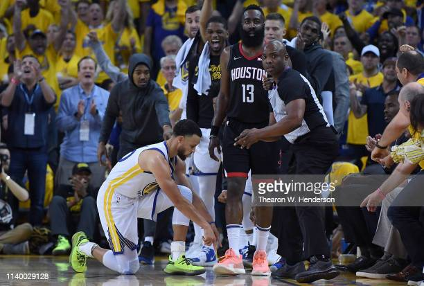 Stephen Curry of the Golden State Warriors points to the line that James Harden of the Houston Rockets stepped on turning the ball over to the...