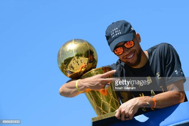 Stephen Curry of the Golden State Warriors poses for a photo with the Larry O'Brien Trophy during the Victory Parade and Rally on June 15 2017 in...