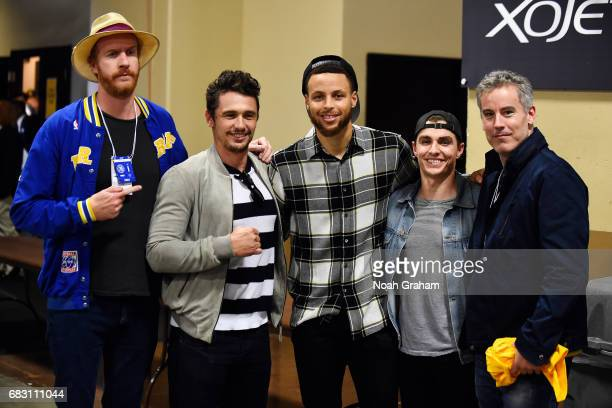 Stephen Curry of the Golden State Warriors poses for a picture with James Franco and Dave Franco during Game One of the Western Conference Finals of...