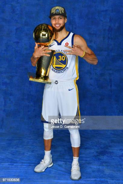 Stephen Curry of the Golden State Warriors poses for a portrait with the Larry O'Brien Trophy after winning Game Four of the 2018 NBA Finals against...