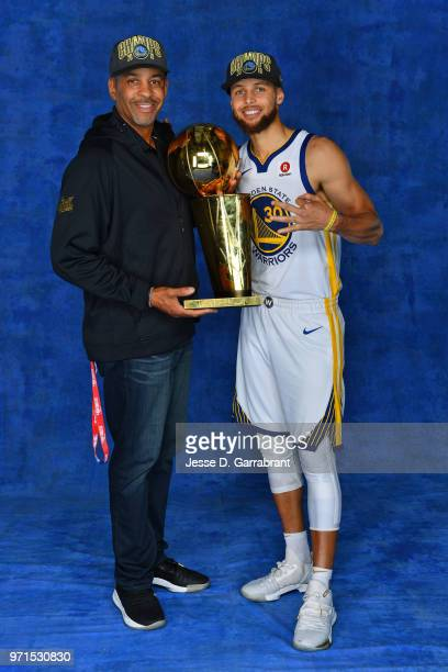 Stephen Curry of the Golden State Warriors poses for a portrait with his father and former NBA player Dell Curry with Larry O'Brien Trophy after...