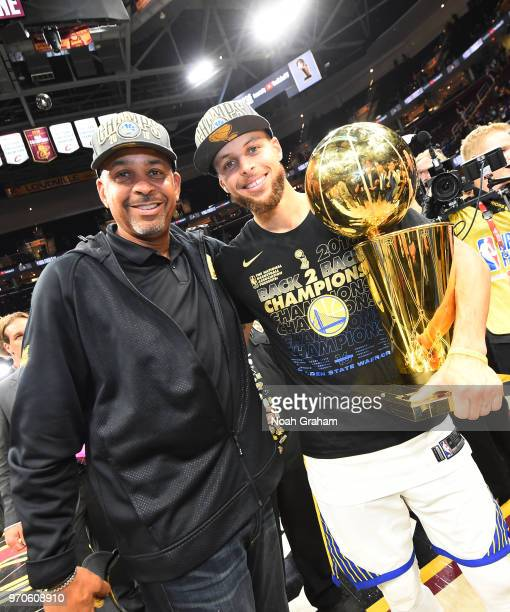 Stephen Curry of the Golden State Warriors poses with Larry O'Brien Championship Trophy and former NBA player Dell Curry after the win against the...