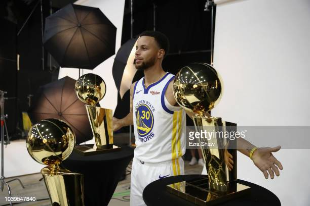 Stephen Curry of the Golden State Warriors poses with three Larry O'Brien NBA Championship Trophies during the Golden State Warriors media day on...