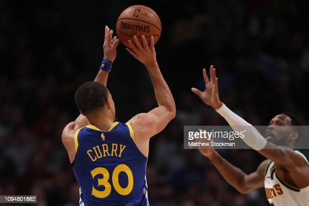 Stephen Curry of the Golden State Warriors puts up a shot over Will Barton of the Denver Nuggets at the Pepsi Center on January 15 2019 in Denver...
