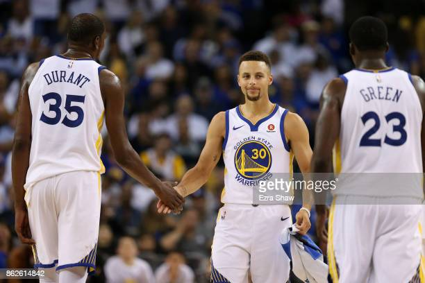 Stephen Curry of the Golden State Warriors reacts after a play against the Houston Rockets with Kevin Durant and Draymond Green during their NBA game...