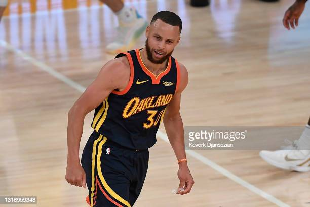 Stephen Curry of the Golden State Warriors reacts after hitting a three-point shot during the final seconds of the first half of an NBA Tournament...