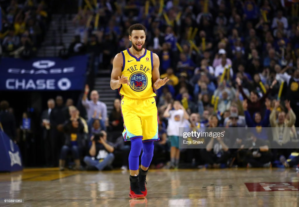 Stephen Curry #30 of the Golden State Warriors reacts after Kevin Durant #35 made a basket against the Minnesota Timberwolves at ORACLE Arena on January 25, 2018 in Oakland, California.