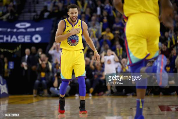 Stephen Curry of the Golden State Warriors reacts after Kevin Durant made a basket against the Minnesota Timberwolves at ORACLE Arena on January 25...