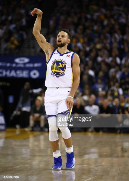 Stephen Curry of the Golden State Warriors reacts after making a basket against the New York Knicks at ORACLE Arena on January 23 2018 in Oakland...