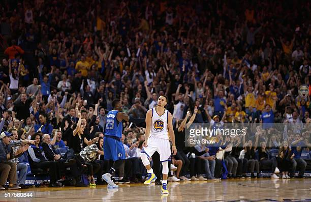 Stephen Curry of the Golden State Warriors reacts after making a shot near half court at the end of the first half of their game against the Dallas...
