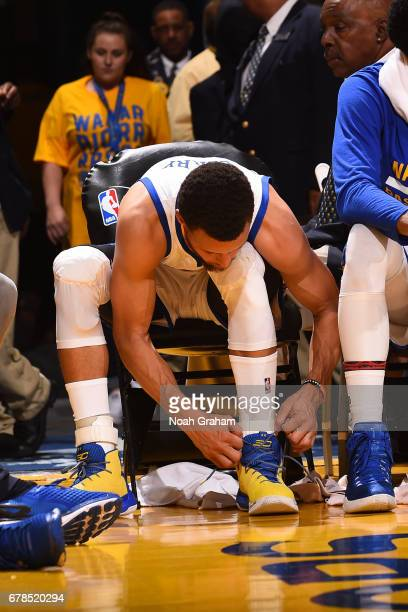 Stephen Curry of the Golden State Warriors retapes his ankle and ties his shoes during Game One of the Western Conference Semifinals against the Utah...