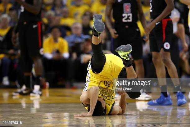 Stephen Curry of the Golden State Warriors rolls on his back after being fouled by the LA Clippers during Game Two of the first round of the 2019 NBA...