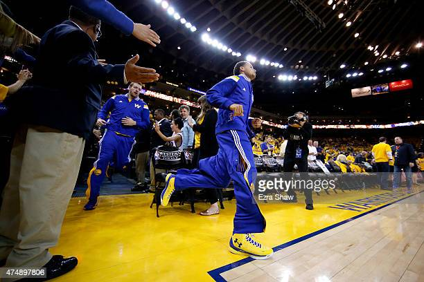 Stephen Curry of the Golden State Warriors runs onto the court to take on the Houston Rockets before game five of the Western Conference Finals of...