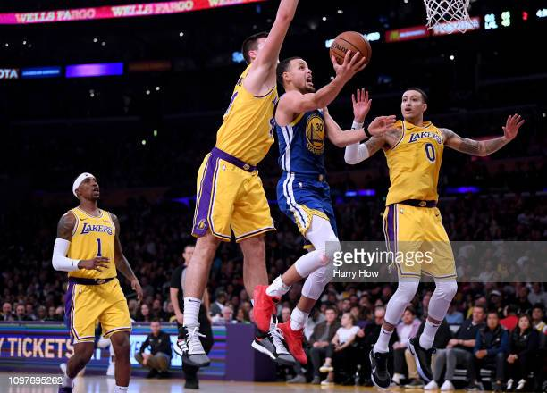 Stephen Curry of the Golden State Warriors scores on a layup as he is fouled by Ivica Zubac of the Los Angeles Lakers as Kyle Kuzma makes a play for...