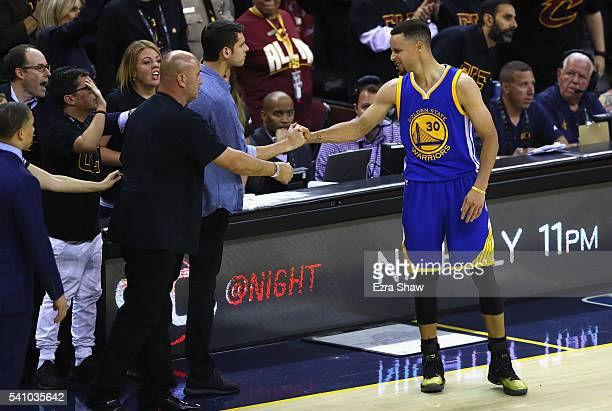 Stephen Curry of the Golden State Warriors shakes hands with fans after throwing his mouthguard in the fourth quarter against the Cleveland Cavaliers...