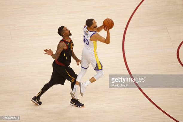 Stephen Curry of the Golden State Warriors shoots a three point basket while guarded by JR Smith of the Cleveland Cavaliers in Game Four of the 2018...