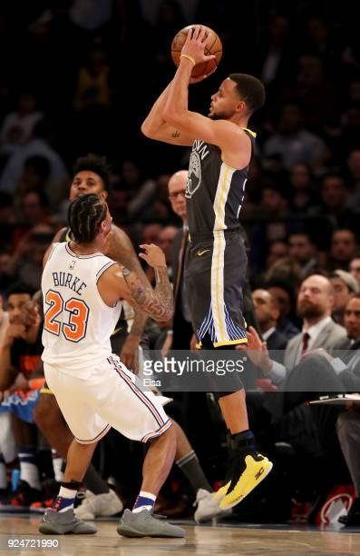 Stephen Curry of the Golden State Warriors shoots a three point shot over Trey Burke of the New York Knicks at Madison Square Garden on February 26...