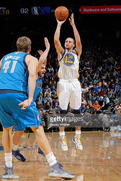 Stephen Curry of the Golden State Warriors shoots a three pointer against Jose Calderon of the Dallas Mavericks on December 11 2013 at Oracle Arena...
