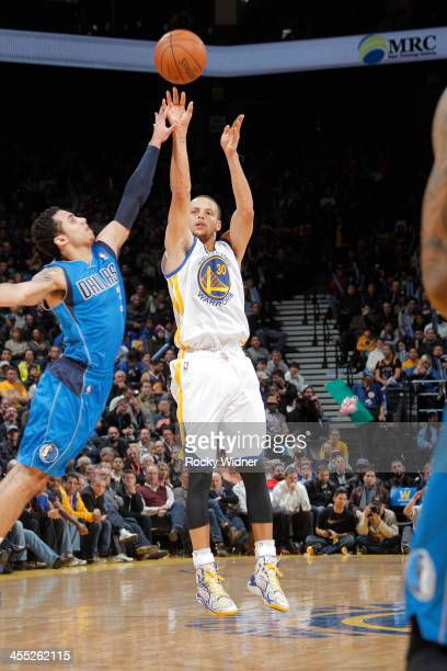 Stephen Curry of the Golden State Warriors shoots a three pointer against Shane Larkin of the Dallas Mavericks on December 11 2013 at Oracle Arena in...