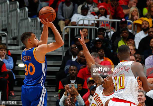 Stephen Curry of the Golden State Warriors shoots a threepoint basket against Jeff Teague and Tim Hardaway Jr #10 of the Atlanta Hawks at Philips...