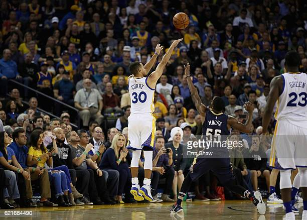 Stephen Curry of the Golden State Warriors shoots a threepoint basket over E'Twaun Moore of the New Orleans Pelicans at ORACLE Arena on November 7...
