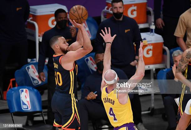 Stephen Curry of the Golden State Warriors shoots a three-pointer as Alex Caruso of the Los Angeles Lakers defends during the final seconds of the...