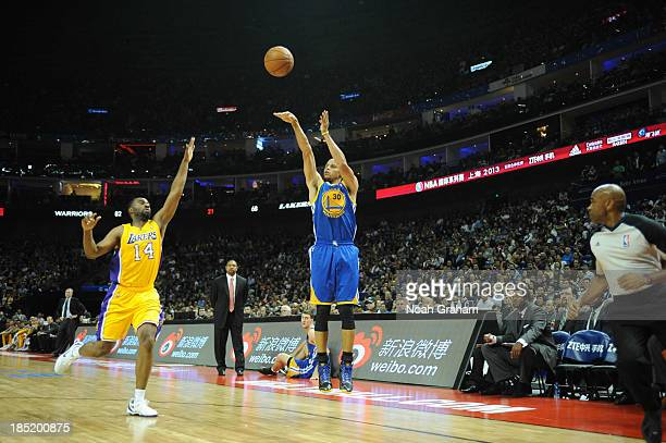 Stephen Curry of the Golden State Warriors shoots against Marcus Landry of the Los Angeles Lakers during the 2013 Global Games on October 18 2013 at...