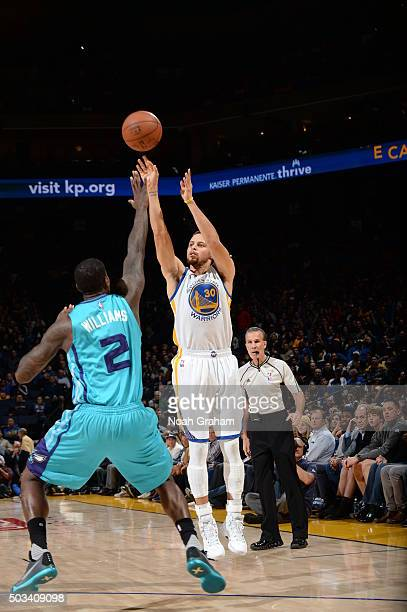 Stephen Curry of the Golden State Warriors shoots against Marvin Williams of the Charlotte Hornets on January 4 2016 at Oracle Arena in Oakland...
