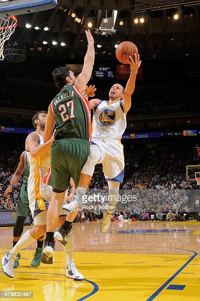 Stephen Curry of the Golden State Warriors shoots against Zaza Pachulia of the Milwaukee Bucks on March 20 2014 at Oracle Arena in Oakland California...