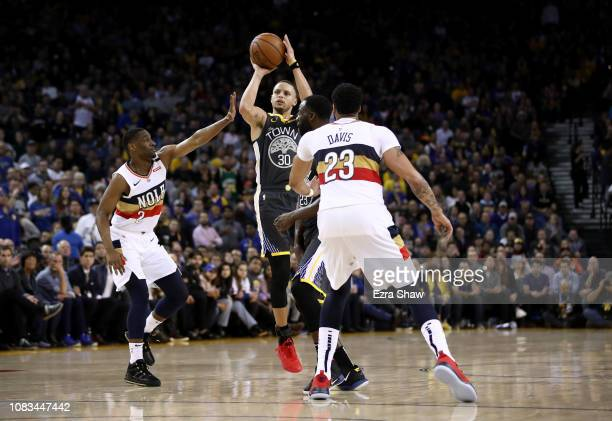 Stephen Curry of the Golden State Warriors shoots over Ian Clark of the New Orleans Pelicans at ORACLE Arena on January 16 2019 in Oakland California...