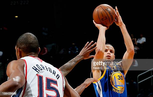 Stephen Curry of the Golden State Warriors shoots over Jeff Teague and Al Horford of the Atlanta Hawks at Philips Arena on December 15 2012 in...