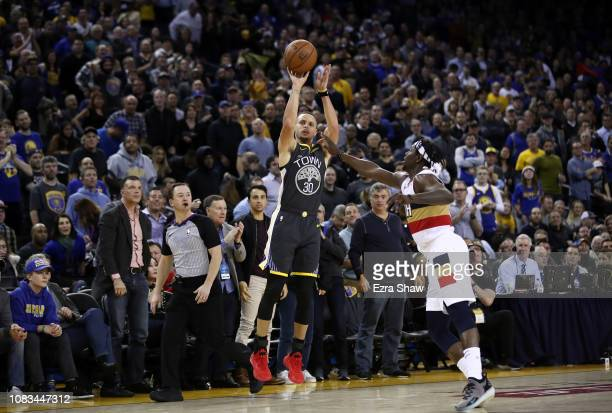 Stephen Curry of the Golden State Warriors shoots over Jrue Holiday of the New Orleans Pelicans at ORACLE Arena on January 16 2019 in Oakland...