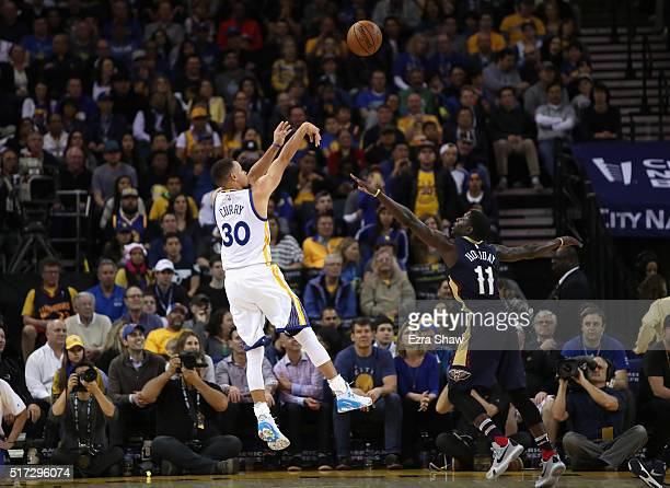 Stephen Curry of the Golden State Warriors shoots over Jrue Holiday of the New Orleans Pelicans at ORACLE Arena on March 14 2016 in Oakland...