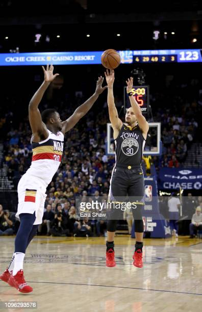 Stephen Curry of the Golden State Warriors shoots over Julius Randle of the New Orleans Pelicans at ORACLE Arena on January 16 2019 in Oakland...