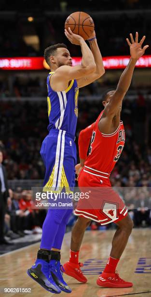Stephen Curry of the Golden State Warriors shoots over Kris Dunn of the Chicago Bulls at the United Center on January 17 2018 in Chicago Illinois...