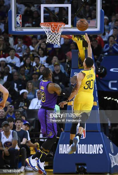 Stephen Curry of the Golden State Warriors shoots over LeBron James of the Los Angeles Lakers during the first half of their NBA Basketball game at...