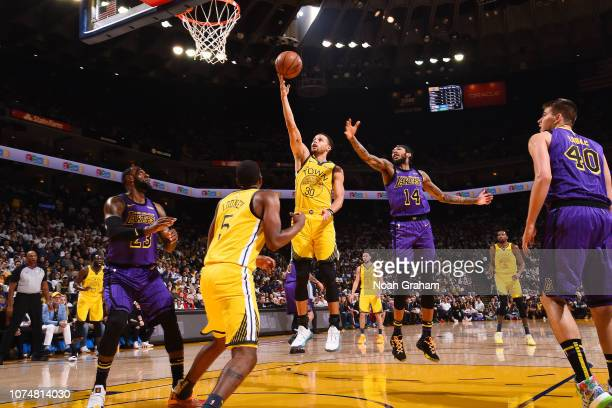 Stephen Curry of the Golden State Warriors shoots the ball against the Los Angeles Lakers on December 25 2018 at ORACLE Arena in Oakland California...