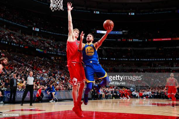Stephen Curry of the Golden State Warriors shoots the ball against Lauri Markkanen of the Chicago Bulls on January 17 2018 at the United Center in...