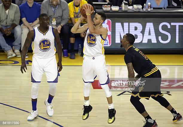 Stephen Curry of the Golden State Warriors shoots the ball as Draymond Green and JR Smith of the Cleveland Cavaliers look on during the first half in...