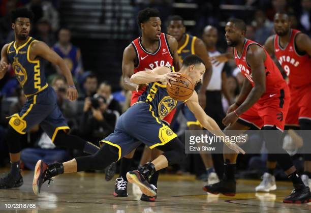 Stephen Curry of the Golden State Warriors slips while being guarded by Kyle Lowry of the Toronto Raptors at ORACLE Arena on December 12 2018 in...