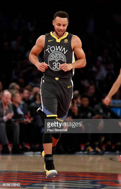 Stephen Curry of the Golden State Warriors smiles as he runs across the Knicks logo during an NBA basketball game against the New York Knicks on...