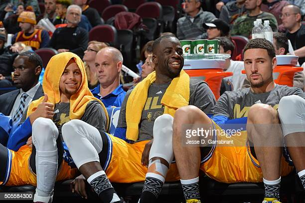 Stephen Curry of the Golden State Warriors smiles while resting on the bench along side Draymond Green an Klay Thompson against the Cleveland...