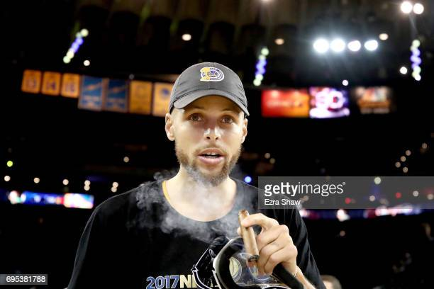 Stephen Curry of the Golden State Warriors smokes a cigar after defeating the Cleveland Cavaliers 129120 in Game 5 to win the 2017 NBA Finals at...