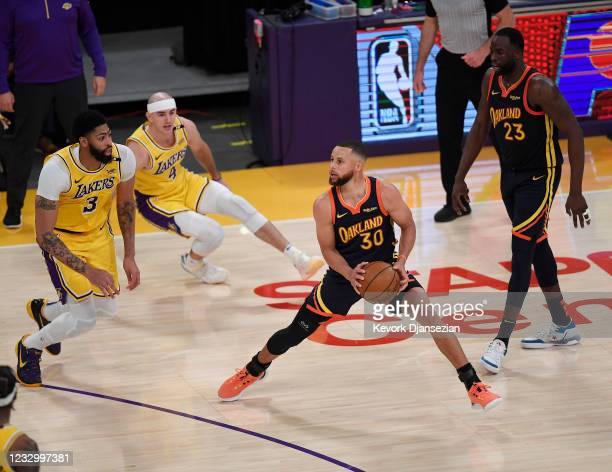 Stephen Curry of the Golden State Warriors steps back to shoot a three point basket against Anthony Davis and Alex Caruso of the Los Angeles Lakers...