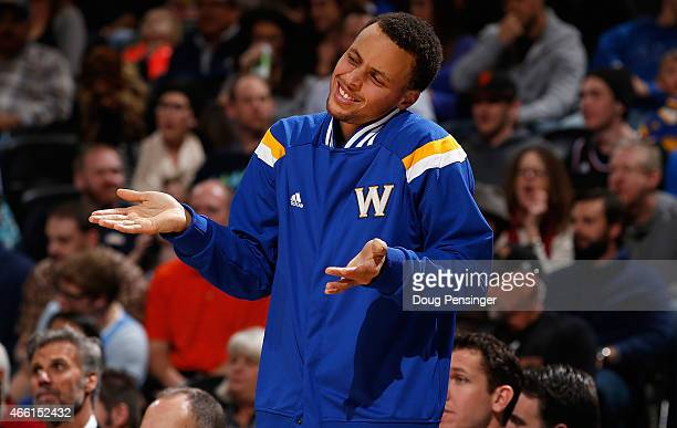 Stephen Curry of the Golden State Warriors supports his teammates from the bench against the Denver Nuggets at Pepsi Center on March 13 2015 in...