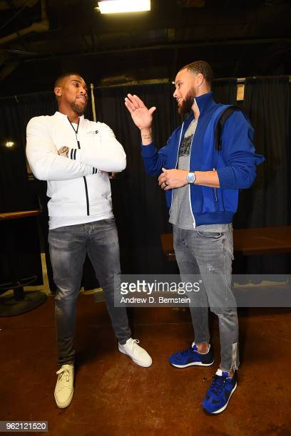 Stephen Curry of the Golden State Warriors talks to Anthony Joshua after the game against the Houston Rockets Game Four of the Western Conference...